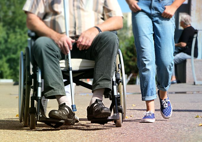 disabled man being assisted by a support assistant